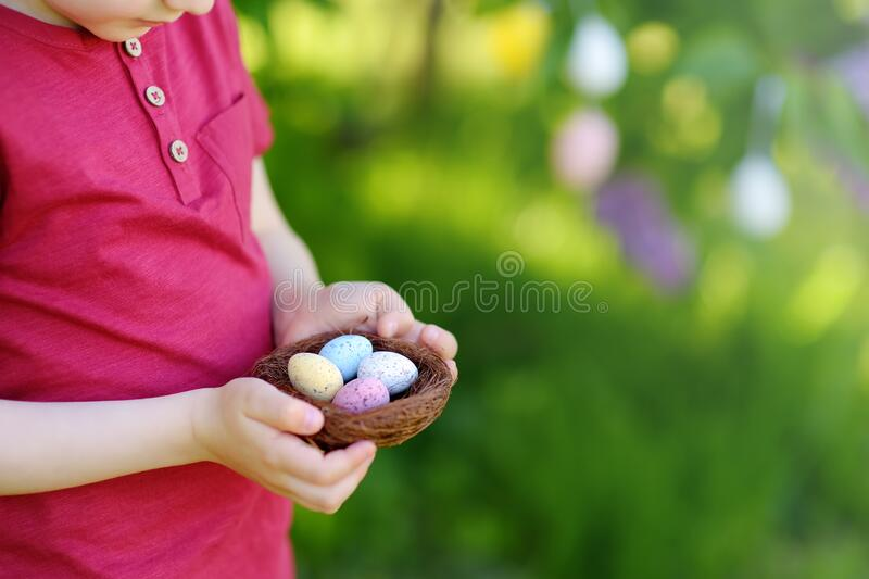 Pretty little boy holding nest with easter eggs in spring park on Easter day royalty free stock photography