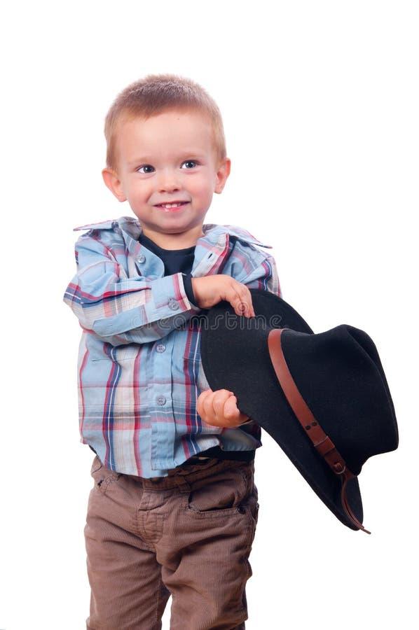 Pretty little boy plays with cowboy hat
