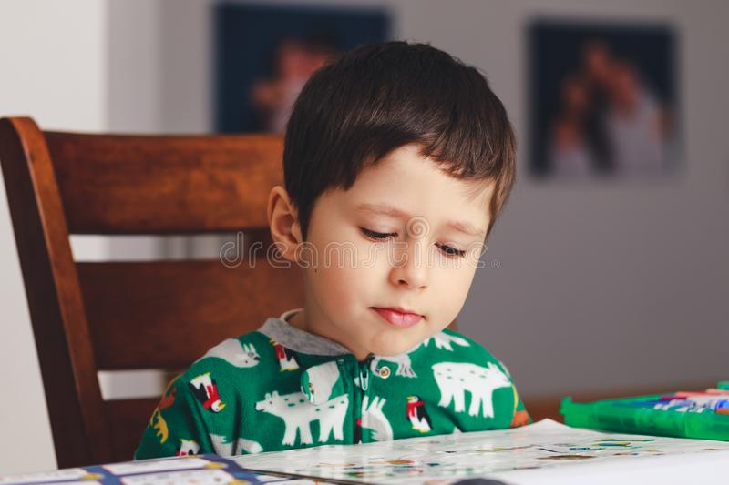 Pretty little boy reading a book while sitting at table, indoor. Shoot. Little boy having fun during studying. Best picture for child education concept royalty free stock images
