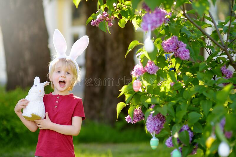 Pretty little boy wearing bunny ears hunting for easter eggs in spring park on Easter day stock photo