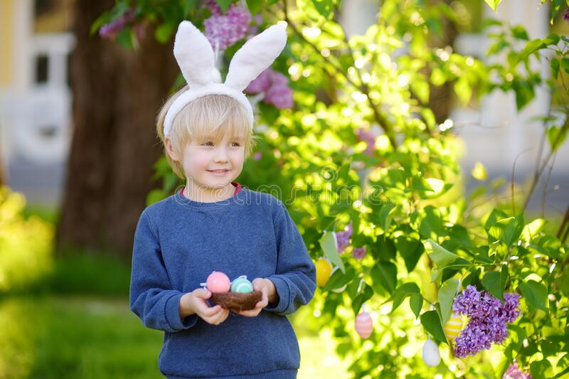 Pretty little boy wearing bunny ears hunting for easter eggs in spring park on Easter day stock image