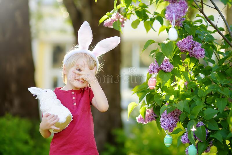 Pretty little boy wearing bunny ears hunting for easter eggs in spring park on Easter day royalty free stock photography