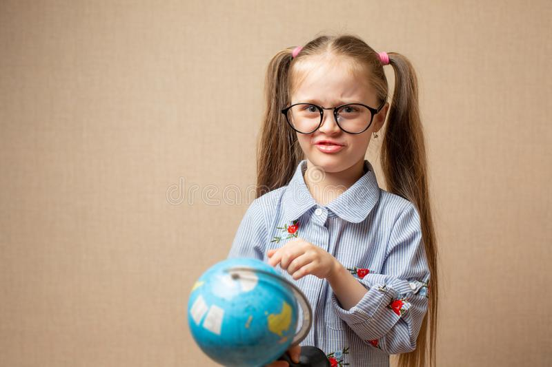 Pretty little child girl in glasses with globe royalty free stock photography
