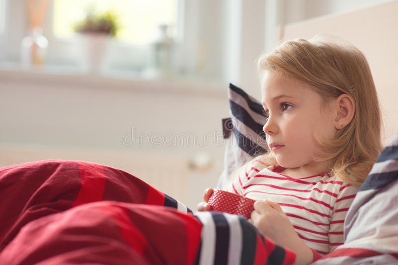 Pretty little child girl laying in bed and drink tea stock photos