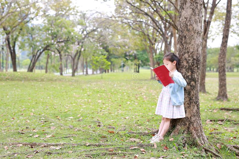 Pretty little child girl reading book in park outdoor standing lean against tree trunk in summer garden stock images