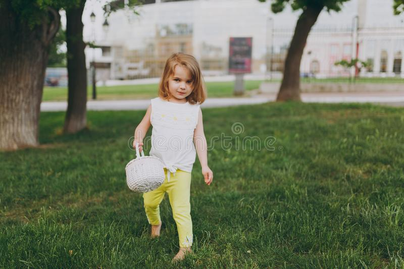 Pretty little cute child baby girl with basket walking, play and have fun on green grass lawn in park. Little kid royalty free stock image