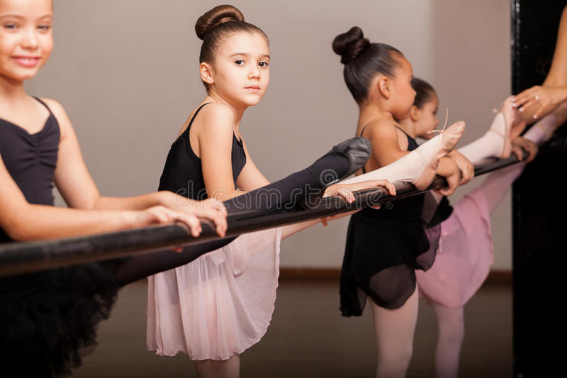 Pretty little dancers using a barre stock photos