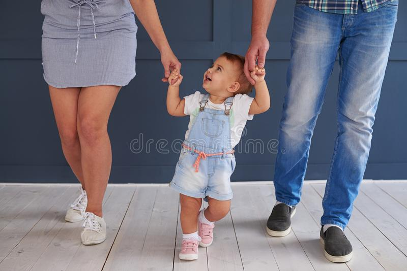 Pretty little daughter holding parent hands while walking in room stock photo