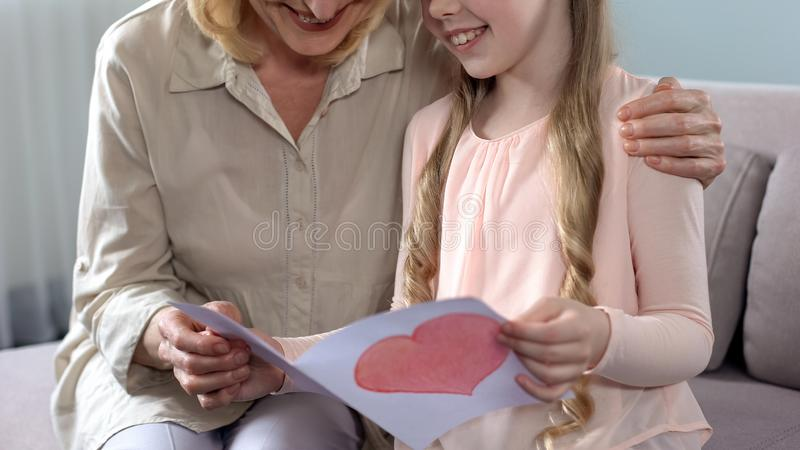 Pretty little female kid presenting handmade greeting card to grandma, birthday royalty free stock photography