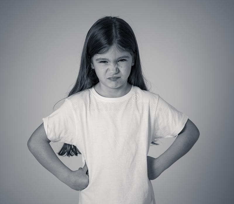 Pretty little girl with a angry facial expression looking mad at the camera. Children emotions royalty free stock photo
