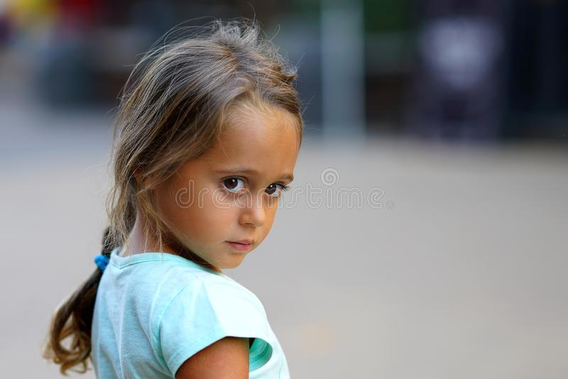 Pretty little girl with big eyes looking seriously royalty free stock photography