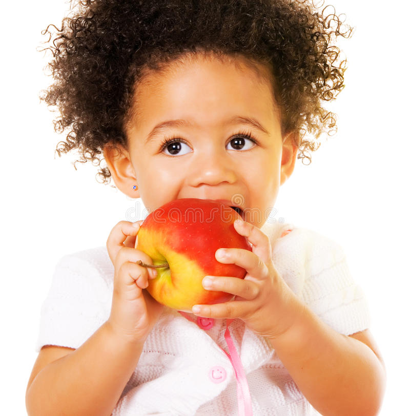 Pretty little girl biting an apple stock images