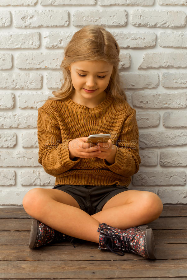 Pretty little girl. Pretty little blonde girl using smartphone while sitting cross-legged against white brick wall royalty free stock photography