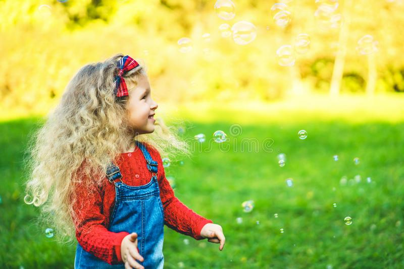 Pretty little girl blowing bubbles in the park. stock image