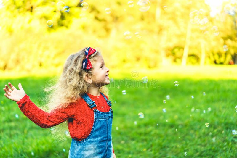Pretty little girl blowing bubbles in the park. stock photos