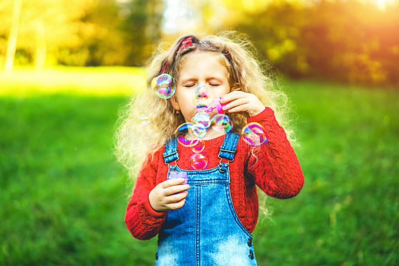 Pretty little girl blowing bubbles in the park. royalty free stock photo