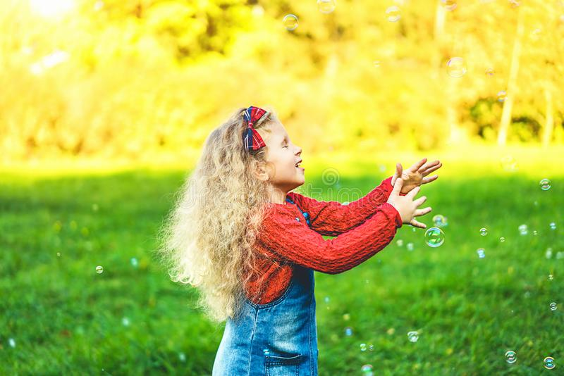 Pretty little girl blowing bubbles in the park. stock photo