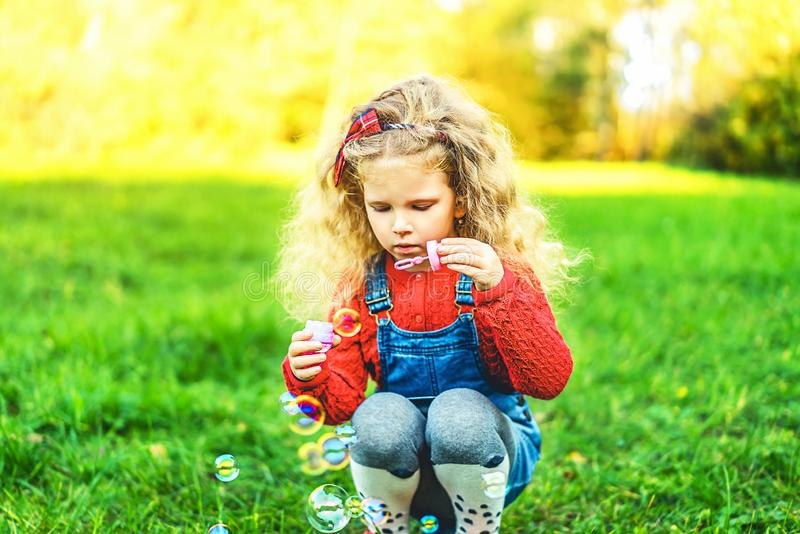 Pretty little girl blowing bubbles in the park. royalty free stock images