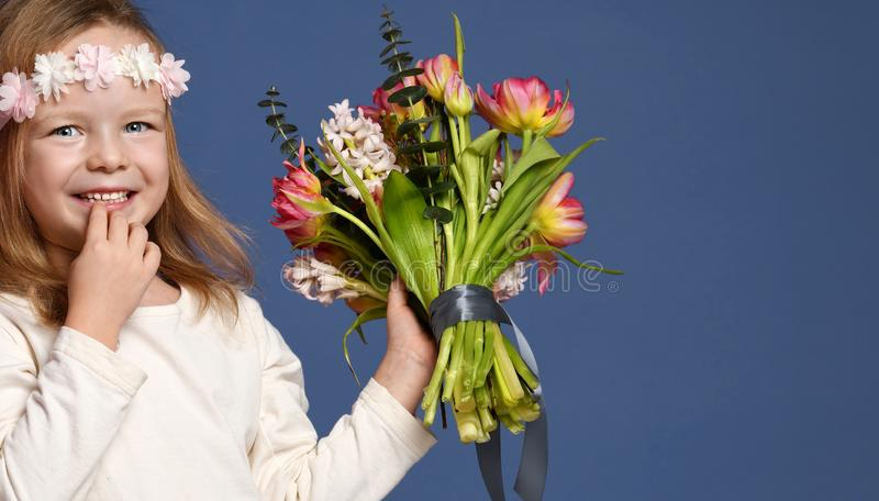 Pretty little girl with bouquet of spring tulips flowers for woman or mothers day 8 march happy smiling royalty free stock photo