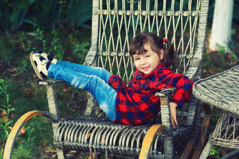 Pretty little girl in a chair in the garden . royalty free stock photo