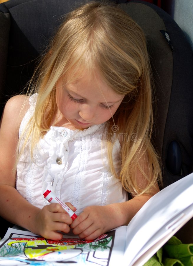 Pretty little girl colouring. Pretty little blond girl colouring in a book stock images