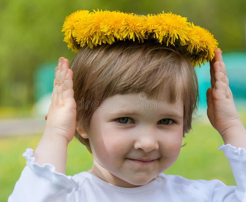 Pretty little girl with crown from dandelions stock photos