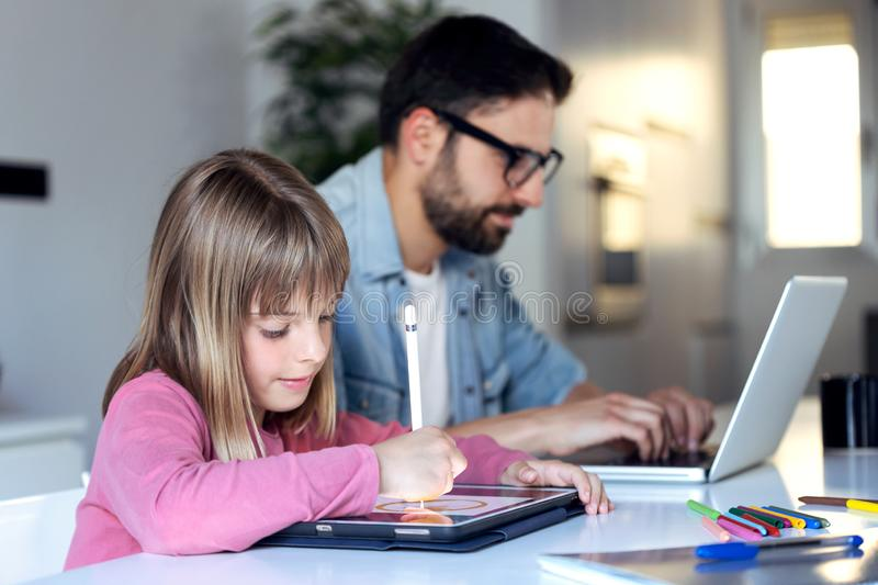 Pretty little girl drawing on her digital tablet while her father working with laptop at home stock image