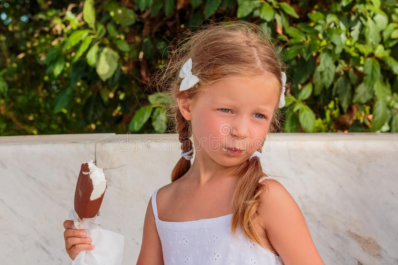 Pretty little girl eating an ice cream outdoors.Portrait of funny blonde child in white dress on nature background stock photography