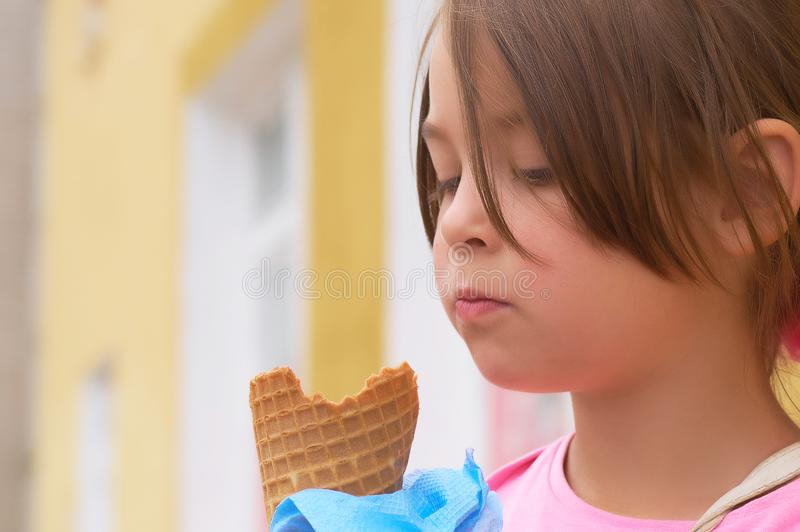 Pretty little girl eating licking big ice cream in waffles cone happy laughing on nature background royalty free stock photos