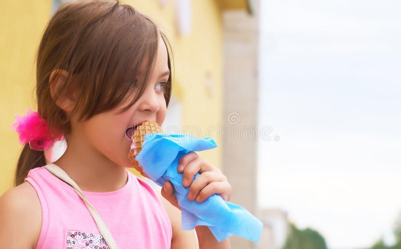 Pretty little girl eating licking big ice cream in waffles cone happy laughing on nature background stock image