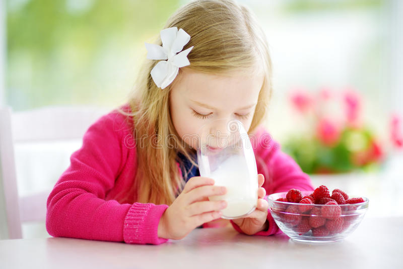 Pretty little girl eating raspberries and drinking milk at home. Cute child enjoying her healthy fresh fruits and berries. Pretty little girl eating raspberries stock photos