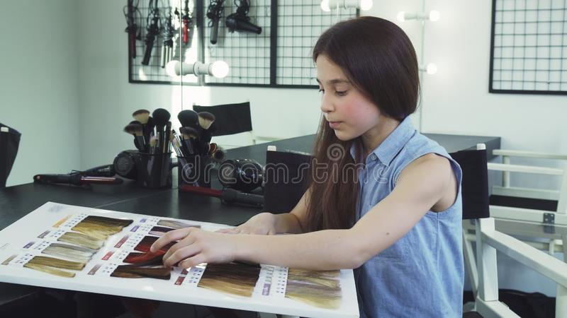 Pretty little girl examining hair dye color chart at the beauty salon. Beautiful little girl looking confused rubbing her chin choosing air color dye at the stock image