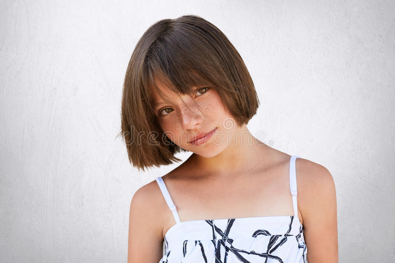 Pretty little girl with freckles, dark eyes and short hairstyle wearing summer white dress posing against white background having. Confident and serious look royalty free stock photography
