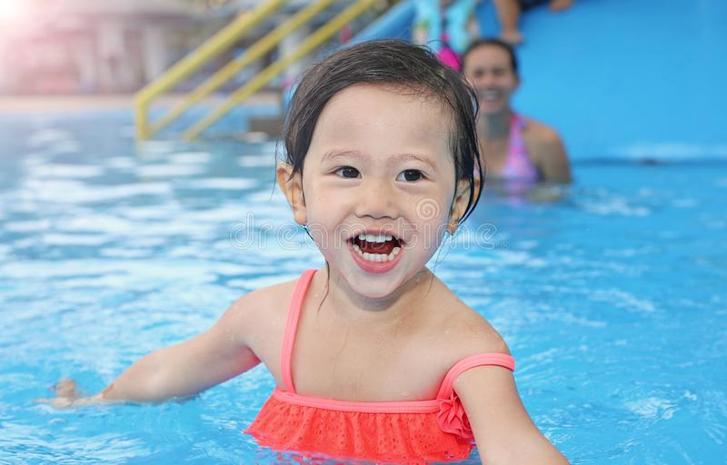 Pretty little girl with her mother in swimming pool outdoors royalty free stock photography