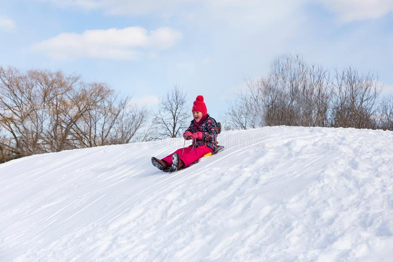 Pretty little girl in her ski suit screaming of joy while sliding down a small snow royalty free stock photography