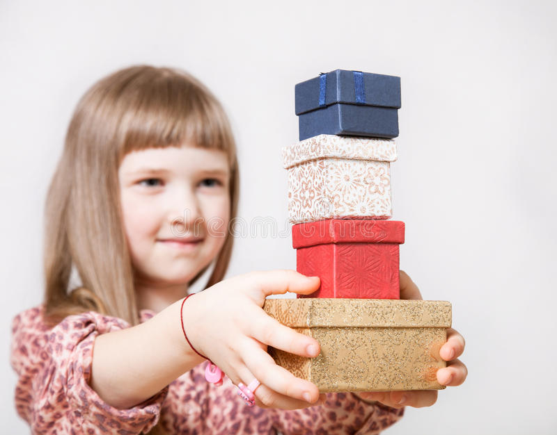 Pretty little girl holding gift boxes royalty free stock photography