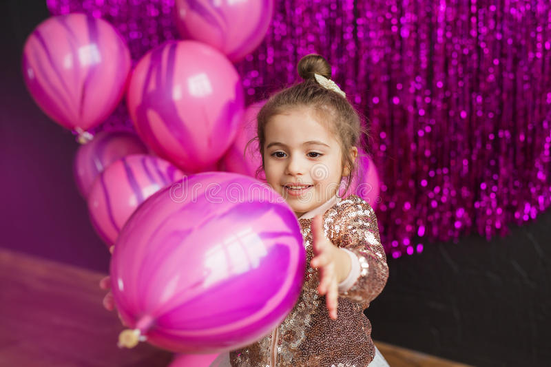 Pretty little girl holds pink balloon at hands. Pretty little girl holds balloon at hands stock image