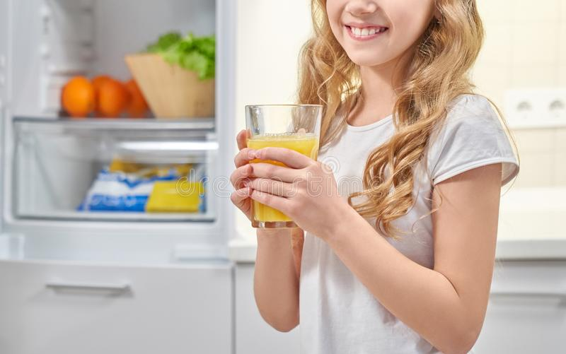 Pretty little girl keeping fresh orange juice and smiling royalty free stock images
