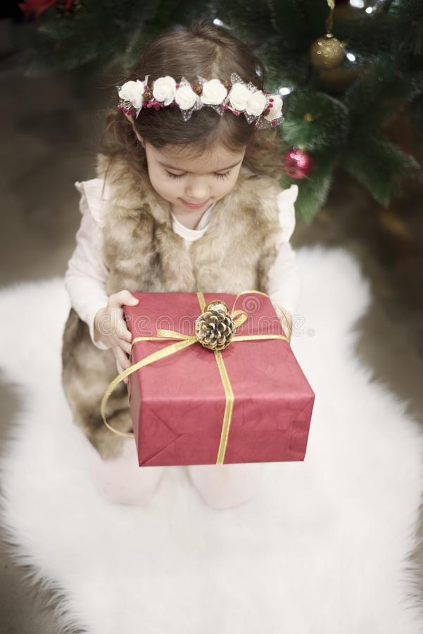 A pretty little girl kid holds a big Christmas gift in front of a Christmas tree. Christmas concept, background royalty free stock image