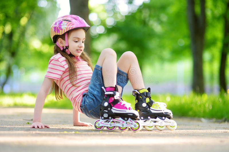 Pretty little girl learning to roller skate on beautiful summer day in a park stock photos