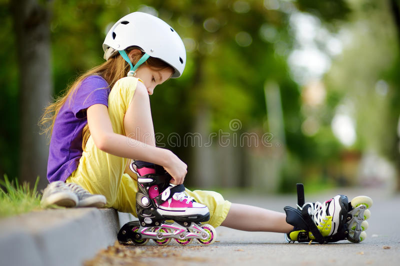 Pretty little girl learning to roller skate on beautiful summer day in a park royalty free stock photography