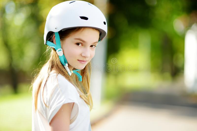 Pretty little girl learning to roller skate on summer day in a park. Child wearing safety helmet enjoying roller skating ride outd. Pretty little girl learning stock photography