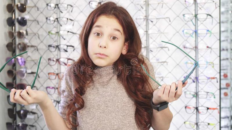 Pretty little girl looking confused choosing between two pairs of sunglasses royalty free stock photography