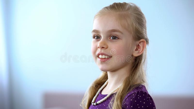 Pretty little girl with pearl necklace looking in mirror, enjoying reflection royalty free stock photo