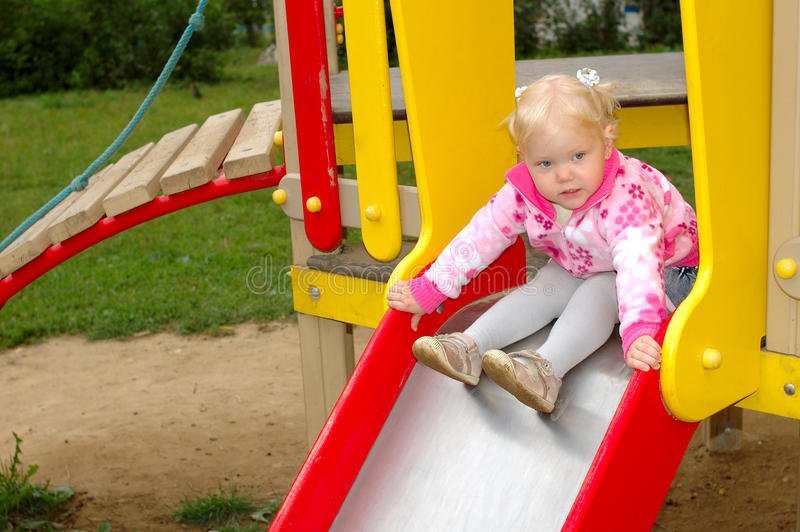 Pretty little girl play on playground in the park. stock photos