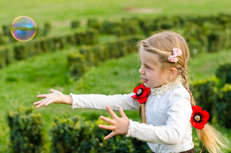 Pretty little girl is playing with bubbles in a park. royalty free stock image