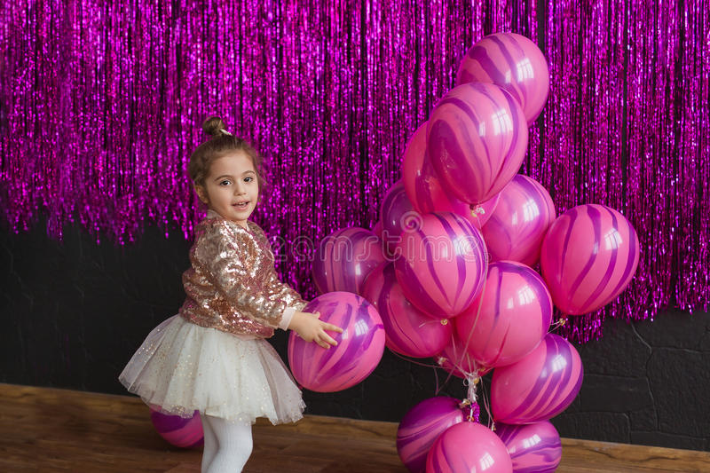 Pretty little girl plays with pink balloons royalty free stock photos