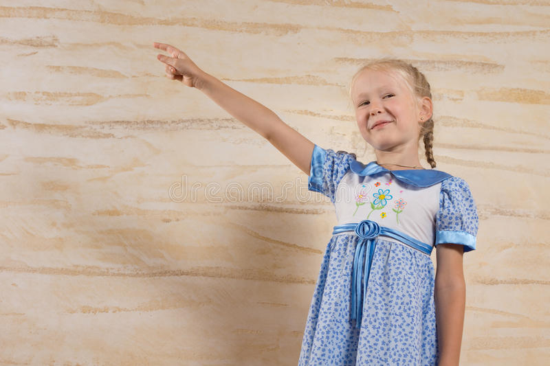Pretty little girl pointing with a pleased smile stock image
