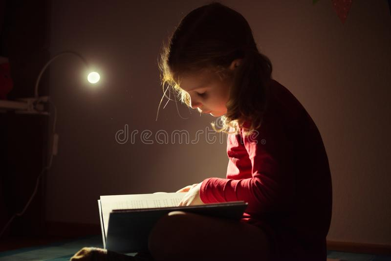 Pretty little girl reading book in her hiding place with flashlight at darkness royalty free stock photo
