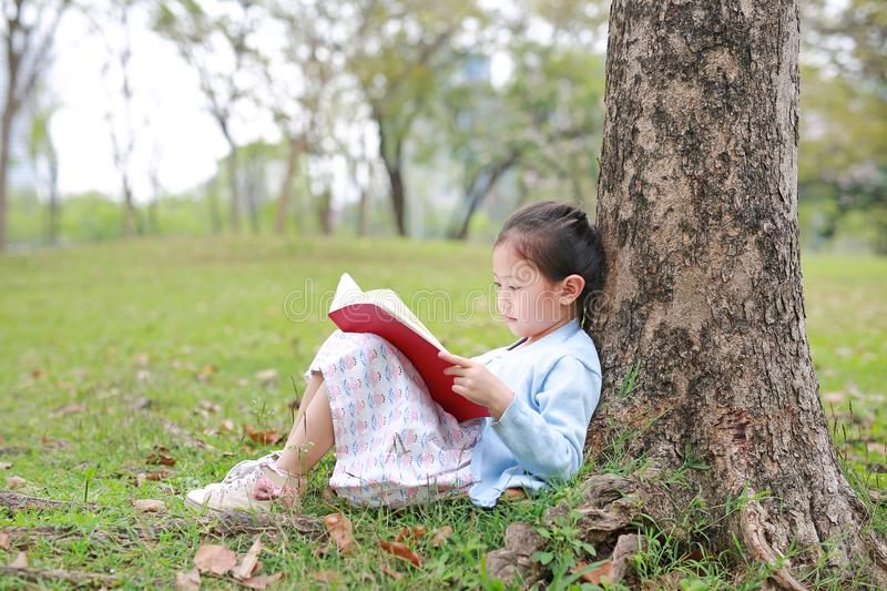 Pretty little girl reading a book sitting under a tree outdoor garden at summer day stock images